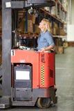 Mulher que conduz o caminhão de empilhadeira no armazém Imagem de Stock