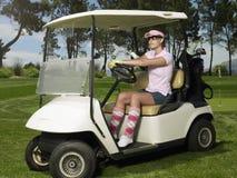 Mulher que conduz o carrinho de golfe Fotografia de Stock Royalty Free