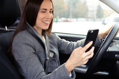 Mulher que conduz o carro e que usa seu smartphone Imagens de Stock