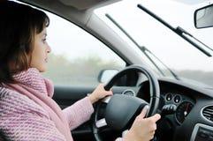 Mulher que conduz o carro na chuva Fotografia de Stock Royalty Free