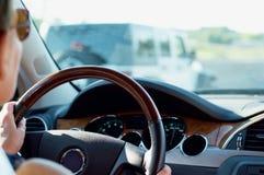 Mulher que conduz o carro na estrada Fotografia de Stock Royalty Free
