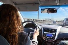 Mulher que conduz o carro na estrada, vista interna Imagens de Stock