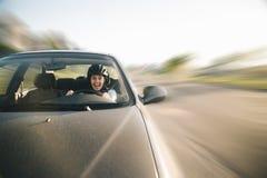 Mulher que conduz o carro no capacete com horror em sua cara foto de stock