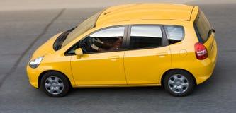Mulher que conduz o carro pequeno amarelo foto de stock royalty free