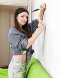 Mulher que conduz o parafuso na parede fotografia de stock royalty free
