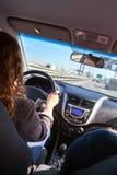 Mulher que conduz o veículo na estrada, vista interna Imagens de Stock