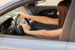 Mulher que conduz um carro com mão no botão de chifre Imagem de Stock