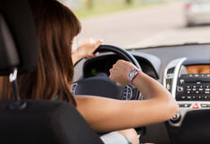 Mulher que conduz um carro e que olha o relógio Imagens de Stock Royalty Free