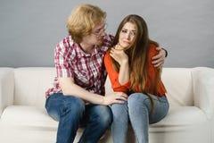 Mulher que confia ao homem no sofá Fotografia de Stock Royalty Free