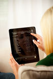 Mulher que consulta através da lista da música no iPad 1 de Apple Fotografia de Stock Royalty Free