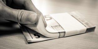 Mulher que conta uma pilha de cinco contas do Euro foto de stock royalty free