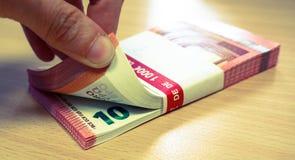 Mulher que conta uma pilha de dez contas do Euro imagens de stock royalty free