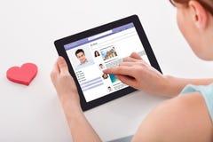 A mulher que conversa em trabalhos em rede sociais situa usando a tabuleta digital Imagens de Stock