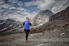 Mulher que corre abaixo da estrada e no fundo uma paisagem montanhosa dos cumes italianos fotos de stock royalty free