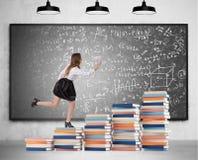 Mulher que corre acima escadas do livro Imagens de Stock