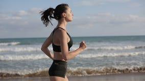 Mulher que corre apenas no por do sol bonito na praia