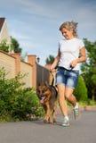 Mulher que corre com seu cão Fotografia de Stock Royalty Free