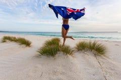 Mulher que corre e que pula com bandeira australiana fotografia de stock