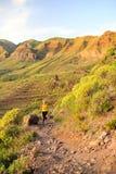 Mulher que corre em montanhas rochosas no por do sol do verão Fotografia de Stock