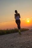 Mulher que corre em uma estrada da montanha no por do sol do verão imagens de stock