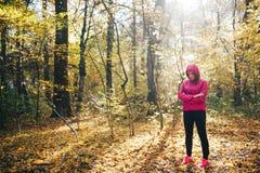 Mulher que corre em uma estrada de floresta durante o nascer do sol Imagens de Stock Royalty Free