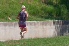 Mulher que corre em uma fuga ao lado de um muro de cimento cercado pela grama Fotografia de Stock