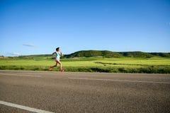 Mulher que corre na estrada do campo Fotografia de Stock