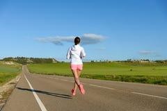 Mulher que corre na estrada secundária Imagem de Stock Royalty Free