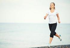 Mulher que corre na praia foto de stock royalty free