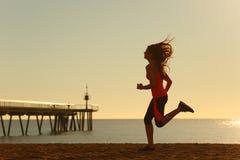 Mulher que corre na praia no nascer do sol imagem de stock royalty free