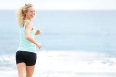 Mulher que corre na praia que olha para trás movimentando-se Fotos de Stock Royalty Free