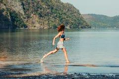 Mulher que corre na praia tropical Fotografia de Stock