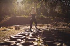 Mulher que corre sobre pneumáticos durante o curso de obstáculo fotos de stock