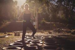 Mulher que corre sobre pneumáticos durante o curso de obstáculo fotos de stock royalty free
