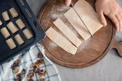 Mulher que corta a massa flocoso na placa de madeira, Foto de Stock