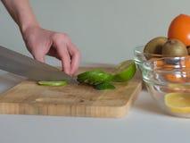 Mulher que corta o cal em partes na placa de madeira Fotos de Stock Royalty Free