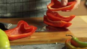 Mulher que corta a pimenta vermelha e que cozinha o quesadilla da batata doce na cozinha video estoque