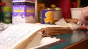 A mulher que cortam acima a manteiga ao ler um livro de receitas velho ou a receita registram na cozinha filme