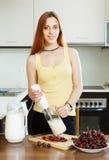 Mulher que cozinha bebidas da leiteria da cereja Imagem de Stock Royalty Free