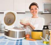 Mulher que cozinha com multicooker em casa Fotos de Stock Royalty Free