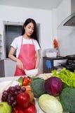Mulher que cozinha e que bate ovos em uma bacia na sala da cozinha Imagens de Stock Royalty Free