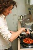 Mulher que cozinha em casa foto de stock