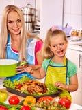 Mulher que cozinha a galinha na cozinha Fotos de Stock