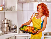 Mulher que cozinha a galinha na cozinha Imagens de Stock