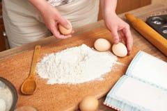 Mulher que cozinha a massa Flour cozendo em um fundo de madeira com utensílios da cozinha Mãos e close up do alimento Quebre um o Fotos de Stock