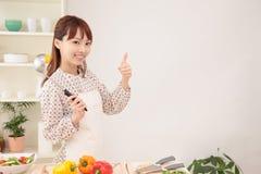 Mulher que cozinha na cozinha com espaço para a cópia Foto de Stock