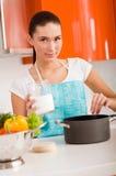 Mulher que cozinha na cozinha, provando a sopa Fotografia de Stock Royalty Free