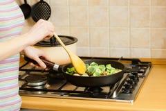 Mulher que cozinha o vegetal congelado fritada da agitação na bandeja Fotografia de Stock