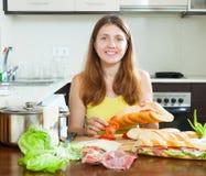 Mulher que cozinha sanduíches com tomate e hamon Fotos de Stock