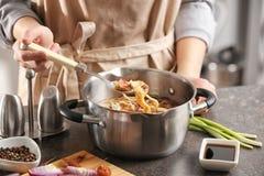Mulher que cozinha a sopa de macarronete da galinha imagens de stock royalty free